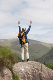 Woman standing on rock cheering after a hike Royalty Free Stock Images