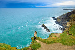 Woman standing on rock cliff by the ocean Co. Cork Ireland Royalty Free Stock Photo