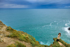 Woman standing on rock cliff by the ocean Co. Cork Ireland Stock Images