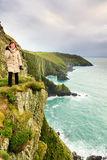 Woman standing on rock cliff by the ocean Co. Cork Ireland Stock Photography