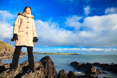 Woman standing on rock cliff at ocean, relaxing Co. Cork Ireland Royalty Free Stock Images