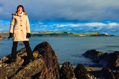 Woman standing on rock cliff at ocean Stock Images