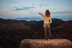 Woman standing on a rock is pointing Royalty Free Stock Photos
