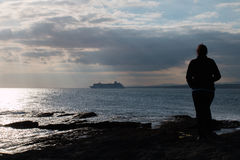 Woman Standing On Rocks And Watching Cruise Ship Stock Image