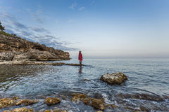Woman standing rocks on waterfront Stock Photo