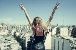 Woman Standing on Rooftop Putting Hands in the Air Under Clear Sky stock photo