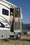 Woman standing in RV doorway at lake Stock Image