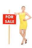 Woman standing by a for sale sign Stock Photography