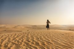 Woman standing in the desert of Qatar royalty free stock image