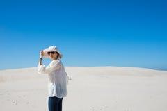 Woman standing on sand dune Stock Photo