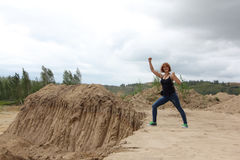 Woman standing at a sandpit in cloudy day Stock Photography