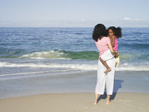Woman standing on sandy beach near water�s edge, looking at Pacific Ocean horizon, carrying daughter (7-9), rear view Stock Images