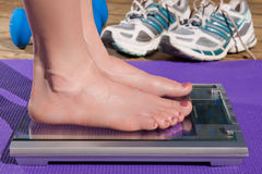 Woman standing on a scale barefoot. Close up of a woman standing barefoot on a scale royalty free stock photography