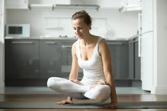 Woman standing in Scale exercise. Sporty attractive woman practicing yoga, standing in Scale exercise, Tolasana pose, working out, wearing white sportswear Royalty Free Stock Image