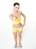 Woman standing on scales and shows the thumbs-up Royalty Free Stock Photos