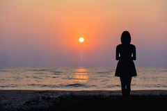 Woman standing by the sea and the sunset Stock Image