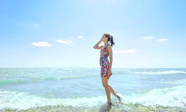 Woman standing in sea waves and holding her glasses Royalty Free Stock Images