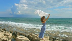 Woman standing on seashore, white scarf waving in the wind. Symbol of freedom. Stock footage stock footage