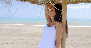 Woman Standing in Shade of Sun Umbrella on Beach. Waist Up of Attractive Smiling Woman with Long Dark Hair Wearing White Tank Top and Standing in Shade of Grass stock footage