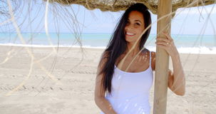 Woman Standing in Shade of Sun Umbrella on Beach. Waist Up of Attractive Smiling Woman with Long Dark Hair Wearing White Tank Top and Standing in Shade of Grass stock video