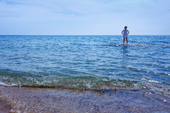 Woman standing in the shallow waters of the sea royalty free stock photos