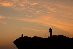Woman standing shooting. On a cliff at sunset Stock Photo