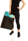 Woman standing with shopping bag full of sports equipment. Isolated Royalty Free Stock Photography