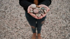 Woman standing on shore of lake holding stones in form of heart