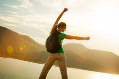 Woman standing on the shore of a mountain lake and raises his ar Royalty Free Stock Photography