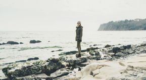 Woman standing on shore. Young woman standing on shore near the sea and looking at camera Royalty Free Stock Photo