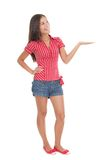Woman standing showing product. Showing product in full length.Young beautiful casual college / university student in summer clothes holding her arm out while Royalty Free Stock Image