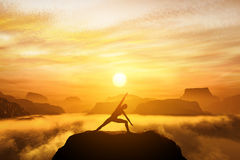 Woman standing in side angle yoga position, meditating. On the top of a mountain above clouds at sunset. Zen, meditation, peace Royalty Free Stock Photo