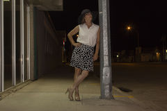 Woman standing on side walk leaning against light post at night time Royalty Free Stock Photos