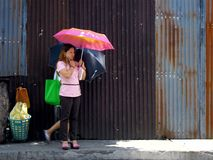 Woman standing on a sidewalk with an umbrella Stock Photo