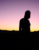 Woman Standing Silhouette. Woman standing against a sunset in the mountains in the desert in silhouette form stock image