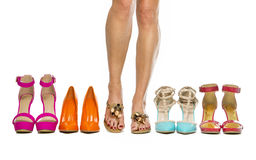 Woman is standing in slippers in between high heels shoes Stock Photo