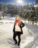 Woman standing in snow. Beautiful blonde woman standing in snow, sunbrust Royalty Free Stock Photo