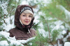 Woman is standing among the snow covered pines. Royalty Free Stock Image