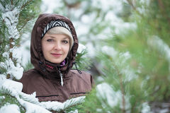Woman is standing among the snow covered pines. Stock Image