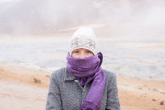 Woman standing in snow storm. Woman with scarf and beanie hat with hot springs in background at Hverir, Iceland Royalty Free Stock Photography
