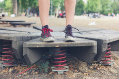 Woman standing on springs in playground Royalty Free Stock Photography