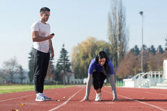 Woman Standing in Starting Position for Running. Handsome Personal Trainer Helping Woman To Sprint on the Running Track in City Park Area - Training and Royalty Free Stock Photo