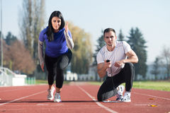 Woman Standing in Starting Position for Running. Handsome Personal Trainer Helping Woman To Sprint on the Running Track in City Park Area - Training and Royalty Free Stock Images