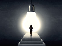 Woman standing on a step in front of a huge light bulb Stock Photo