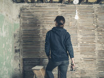 Woman standing on stepladder by wattle and daub wall Royalty Free Stock Image