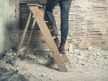 Woman standing on stepladder by wattle and daub wall Stock Photos