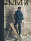 Woman standing on stepladder by wattle and daub wall. A young woman is standing on a stepladder by an old wattle and daub wall Royalty Free Stock Photo