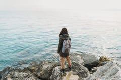 Woman standing on stone on coastline Stock Image