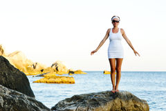 Woman standing on a stone in the sea Stock Image