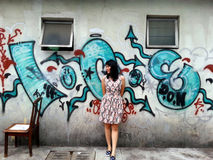 Woman Standing at Street Art Wall Background Royalty Free Stock Image